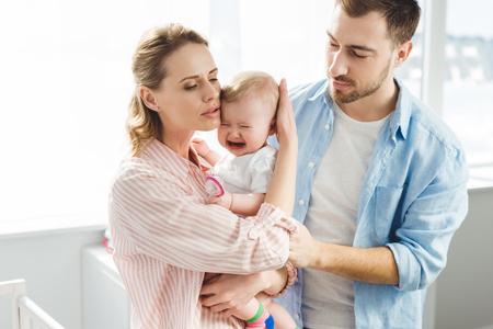 Photo pour Parents trying to calm down crying infant daughter - image libre de droit