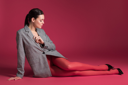 Photo pour Slim woman in red pantyhose and grey jacket lying on red background - image libre de droit