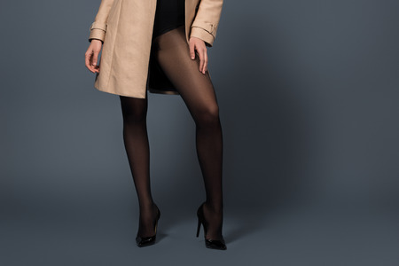 Photo pour Cropped view of woman wearing black tights and beige trench on dark background - image libre de droit