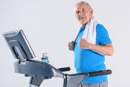 Foto per side view of smiling senior man with towel exercising on treadmill isolated on grey - Immagine Royalty Free