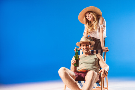 Foto de Blonde woman leaning on chair with man in straw hat holding beer on blue background - Imagen libre de derechos