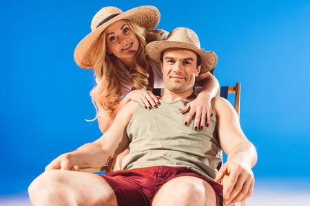 Foto de Woman embracing man resting in deck chair isolated on blue - Imagen libre de derechos