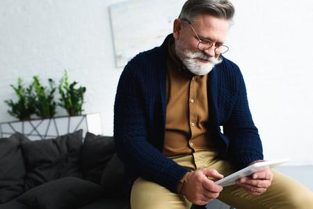 Photo for smiling bearded senior man in eyeglasses using digital tablet at home - Royalty Free Image