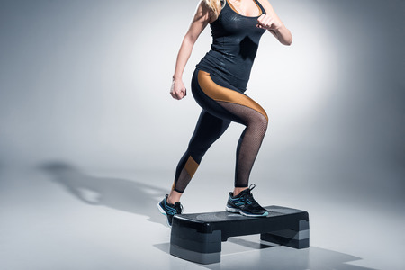 Foto per Young woman exercising on step platform on grey background - Immagine Royalty Free