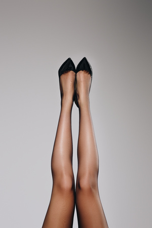 Photo pour Female legs in black stockings isolated on grey background - image libre de droit