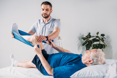 Photo pour rehabilitation therapist assisting senior man exercising with rubber tape on massage table - image libre de droit