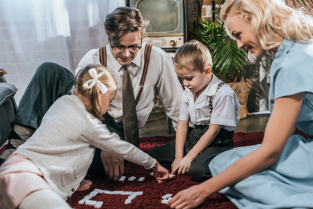 Photo pour smiling old-fashioned family playing dominoes together at home - image libre de droit