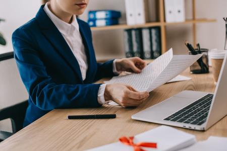 Foto de cropped shot of businesswoman doing paperwork at workplace with laptop in office - Imagen libre de derechos