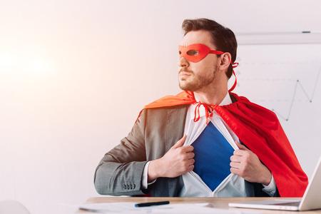 Foto de serious super businessman in mask and cape showing blue shirt in office - Imagen libre de derechos