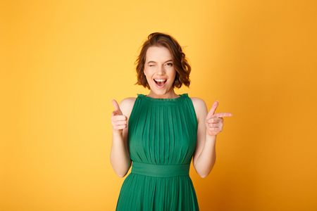 Photo pour portrait of winking woman pointing at camera isolated on orange - image libre de droit