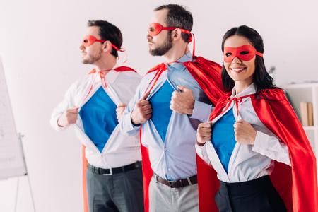 Foto de super businesspeople in masks and capes showing blue shirts in office - Imagen libre de derechos