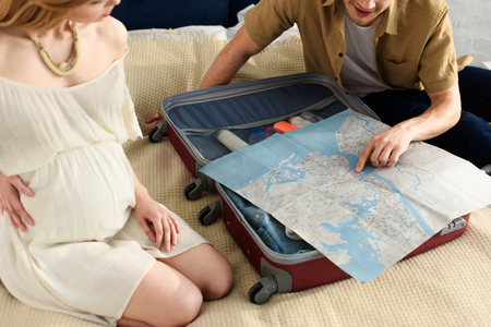 Photo pour cropped view of pregnant woman and husband preparing for vacation and looking at map - image libre de droit