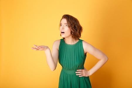 Foto de portrait of shocked woman with outstretched arm isolated on orange - Imagen libre de derechos