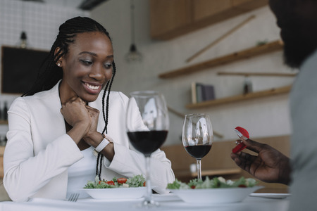 Photo pour partial view of african american man proposing to girlfriend during romantic date in restaurant - image libre de droit