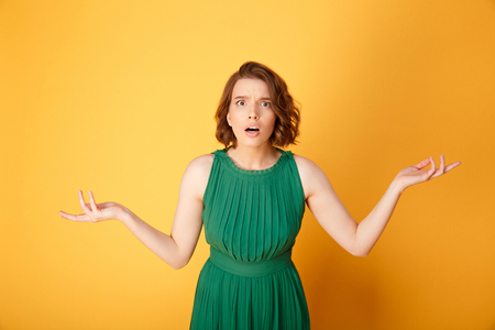 Foto de portrait of young shocked woman with outstretched arms isolated on orange - Imagen libre de derechos