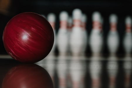 Photo pour close-up shot of red bowling ball on alley in front of pins - image libre de droit
