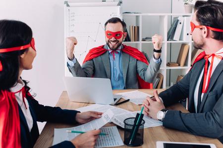 Photo pour super businessman showing yes gesture to colleagues in office - image libre de droit