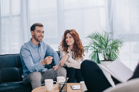 Foto de Smiling young couple sitting on sofa in counselor office - Imagen libre de derechos