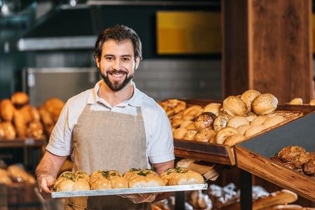 Foto de portrait of smiling shop assistant arranging fresh pastry in supermarket - Imagen libre de derechos