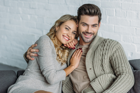Photo pour Portrait of smiling couple hugging and looking at camera on sofa in living room - image libre de droit