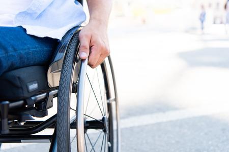 Foto de Cropped image of man using wheelchair on street - Imagen libre de derechos