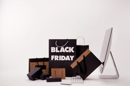 Foto de Side view of computer and various boxes with shopping bags with black Friday sign on white background - Imagen libre de derechos