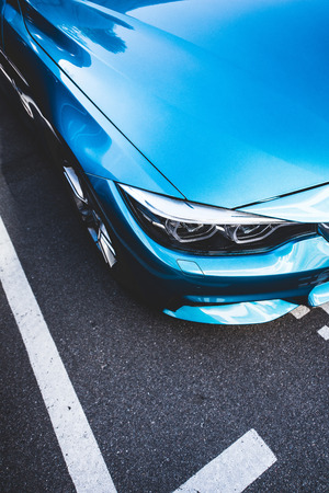 Photo pour Cropped image of blue shiny new car on street - image libre de droit