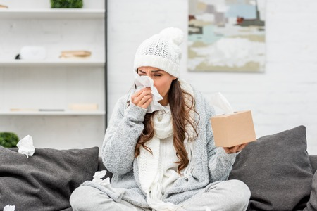 Foto de Diseased young woman in warm clothes sitting on messy couch and sneezing with paper napkins at home - Imagen libre de derechos