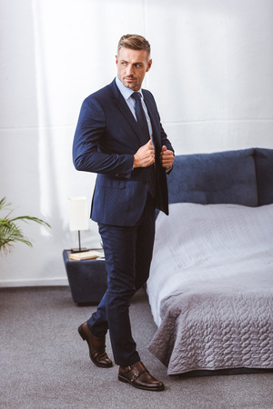 Photo pour Full length view of handsome adult man wearing suit jacket and looking away in bedroom - image libre de droit