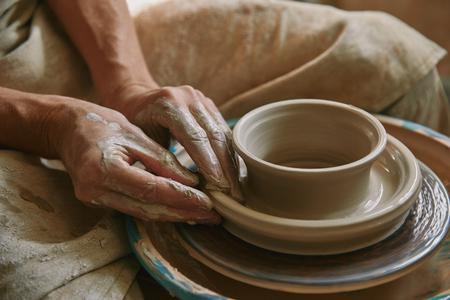 Foto de Close up view of professional potter working on pottery wheel at workshop - Imagen libre de derechos