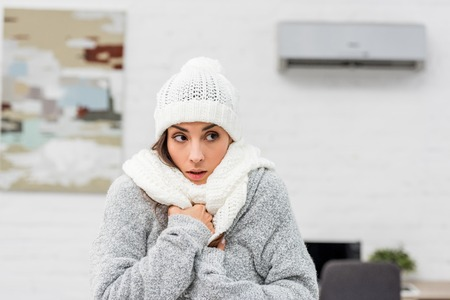 Foto de Close-up portrait of freezing young woman in warm clothes with air conditioner on background - Imagen libre de derechos