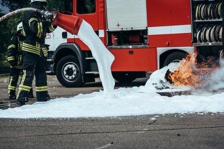 Photo pour Partial view of firefighter extinguishing fire with foam on street - image libre de droit