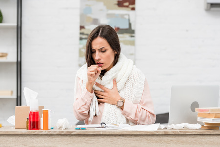 Photo for Sick young businesswoman having cough at workplace - Royalty Free Image