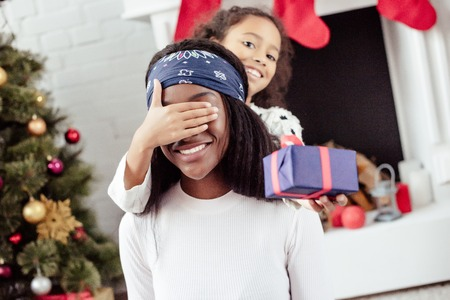 Photo for Smiling African American daughter gifting Christmas present to mother and closing her eyes for surprise at home - Royalty Free Image