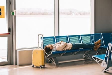 Foto de Young man sleeping on seats while waiting for flight in airport terminal - Imagen libre de derechos