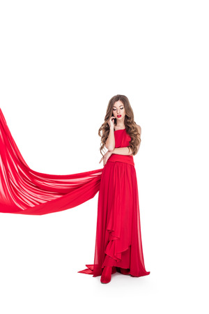 Photo for Beautiful woman posing in red dress with veil, isolated on white background - Royalty Free Image