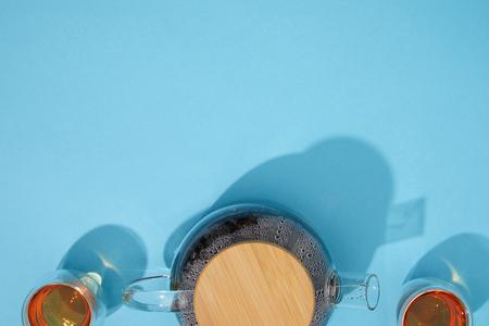 Foto de Top view of teapot and cups with fresh hot tea on blue background - Imagen libre de derechos
