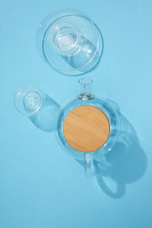 Foto de Top view of empty glass teapot with cup, plate and bowl on blue background - Imagen libre de derechos