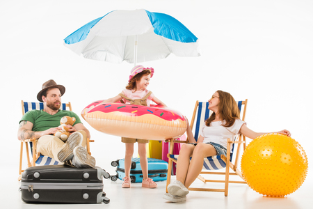 Foto de Happy little kid standing with flotation ring between parents sitting on sun loungers isolated on white background, travel concept - Imagen libre de derechos