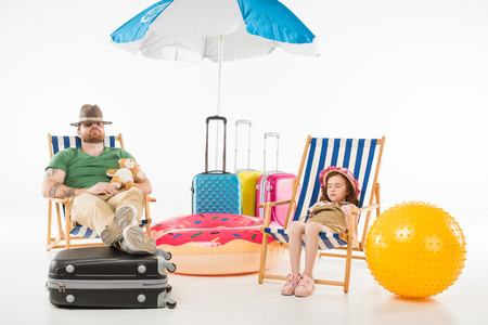 Foto de Father and daughter in hats sleeping in sun loungers isolated on white background, travel concept - Imagen libre de derechos