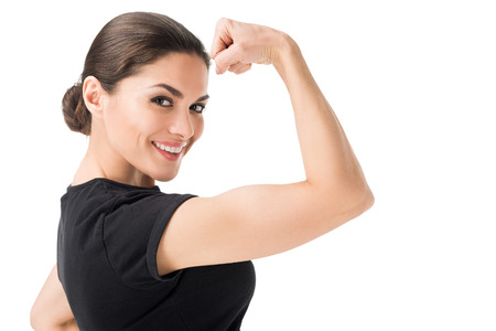 Foto de Young woman showing female power gesture isolated on white background - Imagen libre de derechos
