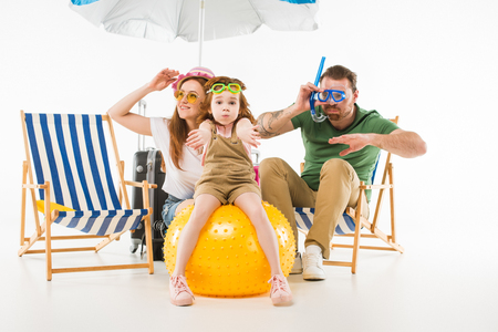 Foto de Family in swimming goggles depicting swim with sunshade, sun loungers and ball isolated on white background, travel concept - Imagen libre de derechos