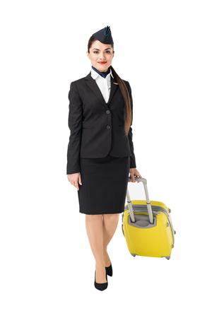 Foto de Stewardess in uniform walking with suitcase isolated on white background - Imagen libre de derechos