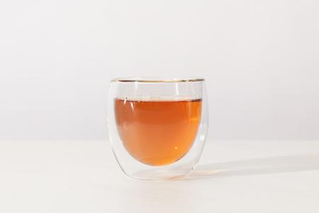 Foto de Close-up view of fresh hot tea in glass cup on grey background - Imagen libre de derechos