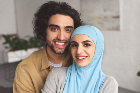 Foto de Portrait of smiling Muslim couple looking at camera at home - Imagen libre de derechos