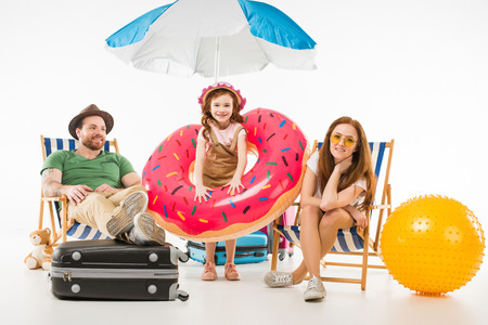 Foto de Little daughter with flotation ring standing between parents sitting on sun loungers isolated on white background, travel concept - Imagen libre de derechos