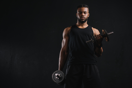 Photo pour Young African American sportsman exercising with dumbbells and looking at camera isolated on black background - image libre de droit