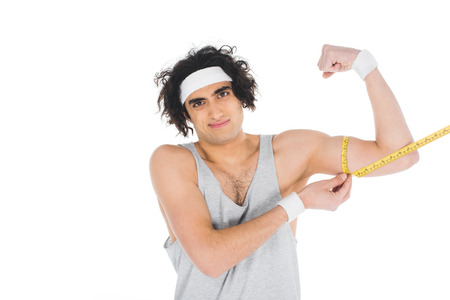 Photo pour Young thin sportsman in headband measuring muscles on hand isolated on white background - image libre de droit