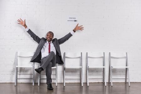 Foto de Smiling African American businessman with outstretched arms waiting for job interview - Imagen libre de derechos