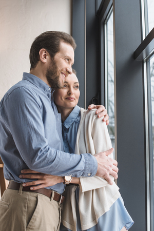 Photo for Portrait of beautiful smiling couple hugging each other and looking out window - Royalty Free Image